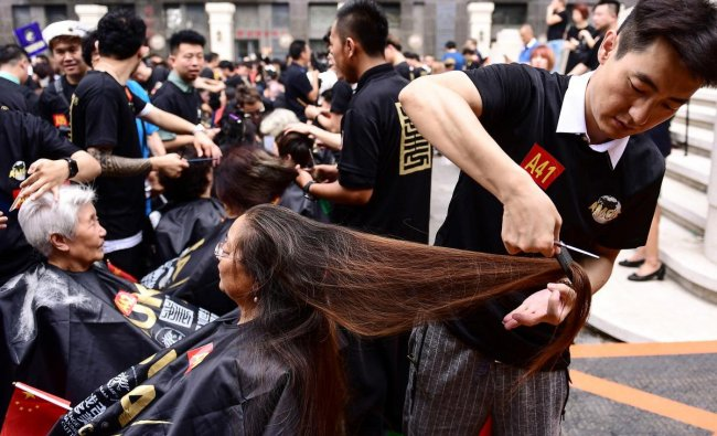 Some 1,400 hairdressers give haircuts as they attempt a Guinness world record for the largest number of people cutting hair at the same time in China. AFP Photo