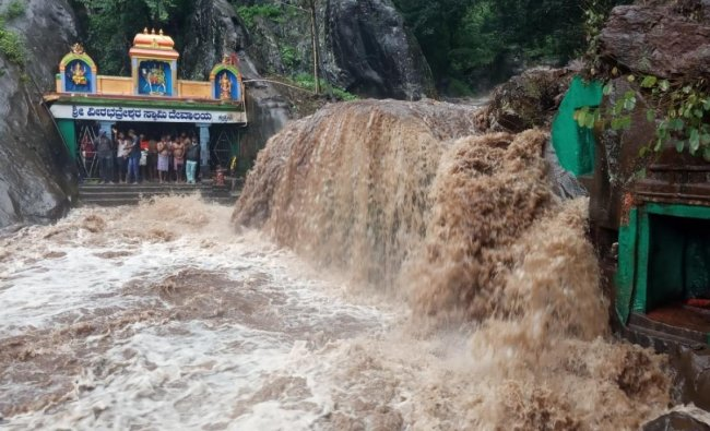 Stranded tourists inside Veerabhadreshwara Swamy Temple amid Kalhathagiri waterfalls in Tarikere. DH Photo