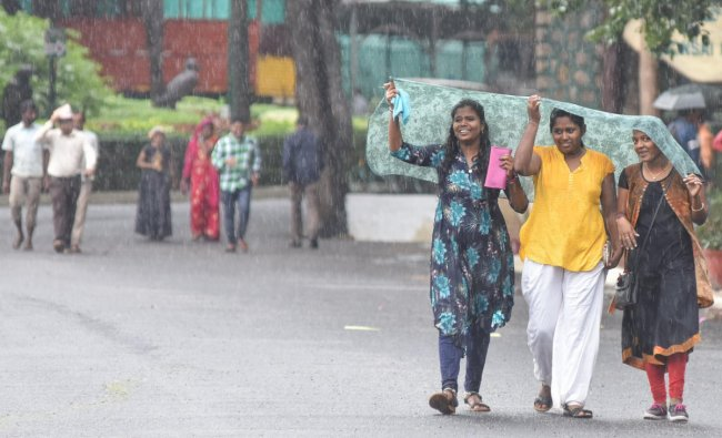 Girls covering by cloth to protect from rain at Lalbagh in Bengaluru on Thursday. (DH Photo   S K Dinesh)