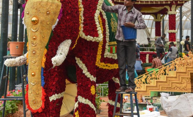 Horticulture Department workers decorating glass house on the eve of 210 Independence Day Flower Show, this year attraction is floral tribute to Maharaja Jayachamaraja Wadiyar. (DH Photo   S K Dinesh)