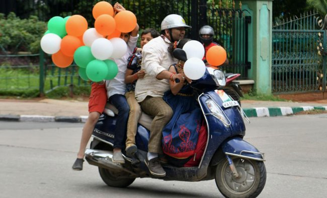 A family ride a scooter on the street as they hold balloons in the colours of the Indian flag during the India\'s 73rd Independence Day, August 15, 2019. (Photo: AFP)