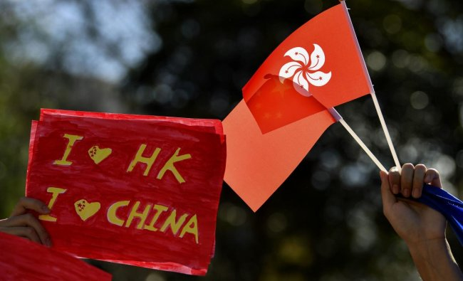 Pro-China activists hold up placards and China with Hong Kong flags while marching on the streets of Sydney on August 17, 2019 (AFP/Saeed KHAN)
