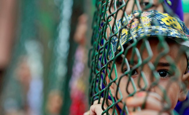 Kashmiri child looks from behind a fence at a protest site after Friday prayers in Srinagar, on August 16, 2019. (REUTERS/Danish Ismail)