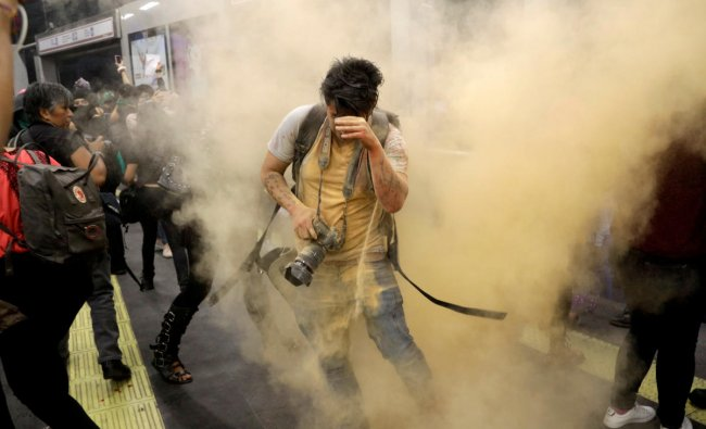 A photographer reacts as demonstrators throw coloured powder during a protest called \