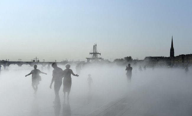 Tourists walk in a mist cloud on the water mirror in Bordeaux, southwestern France, on August 30, 2019 (AFP Photo)