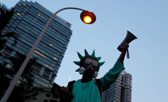 A protestor dressed as the Statue of Liberty, attends a protest in Central, Hong Kong, China. (Photo by Reuters)