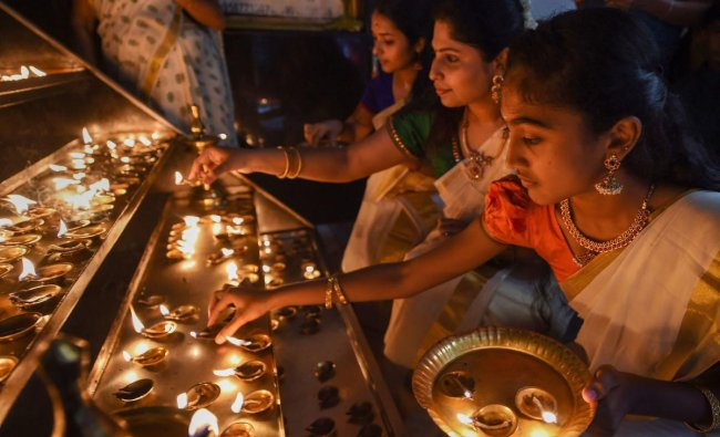 Women light lamps at a temple during Onam celebrations in Chennai. PTI