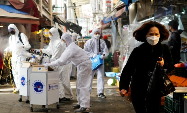 A woman wearing a mask to prevent contracting the coronavirus reacts as employees from a disinfection service company sanitize a traditional market in Seoul, South Korea. (Reuters photo)