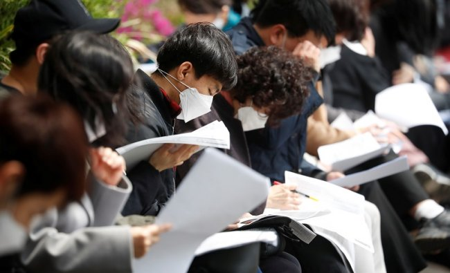 South Korean job seekers wear face masks while preparing for an exam amid social distancing measures to avoid the spread of the coronavirus disease. (AFP Photo)