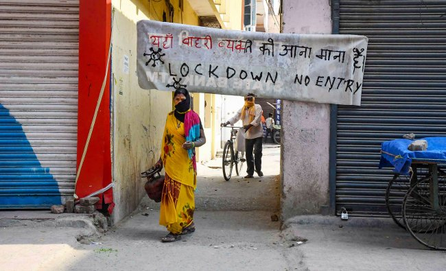 A woman walks past a \'No Entry\' banner set up at an alleyway to restrict the movement of people during the nationwide lockdown, in wake of the coronavirus pandemic, in Patna. (PTI Photo)