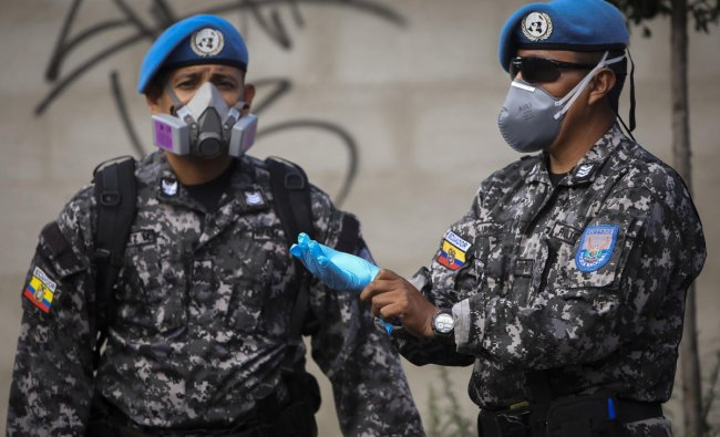 Soldiers wearing protective masks are deployed to provide security as workers of Ecuador\'s Ministry of Economic and Social Inclusion deliver food to low-income families at La Bota neighbourhood in northern Quito. (AFP Photo)