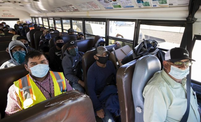 Farm laborers from Fresh Harvest working with an H-2A visa ride the bus. (AFP Photo)