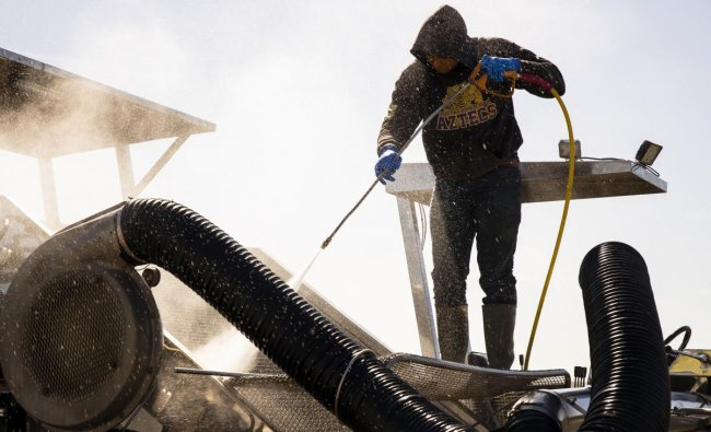 A migrant farm laborer from Fresh Harvest working with an H-2A visa hoses down a spinach harvesting machine after the night shift. (AFP Photo)