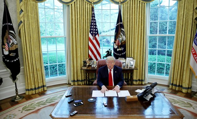 U.S. President Donald Trump looks at his briefing papers as he answers questions during an interview with Reuters about China, the novel coronavirus (COVID-19) pandemic and other subjects in the Oval Office of the White House in Washington, U.S. (Reuters photo)
