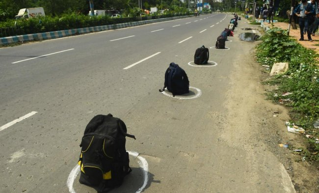 Migrant labourers wait on the shade near their bags placed inside circles marked along a road to maintain social distancing as they wait to board the specially arranged government bus to return to their homes during a government-imposed nationwide lockdown as a preventive measure against the COVID-19 coronavirus, in Kolkata on April 29, 2020. (Photo by Dibyangshu SARKAR / AFP)