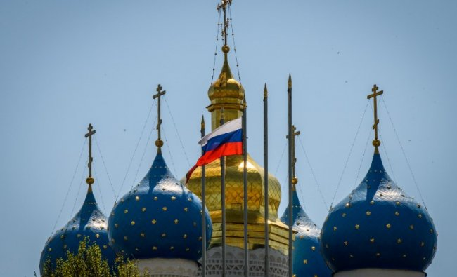 A picture taken on May 15, 2018 shows Russian flag floating in front of church domes in the Kremlin in the Russian city of Kazan. AFP Photo