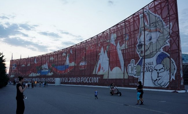 People walk past a huge World Cup 2018-themed banner decorated with an image of Zabivaka, the mascot for the football tournament, in Sochi on June 22, 2017. AFP Photo