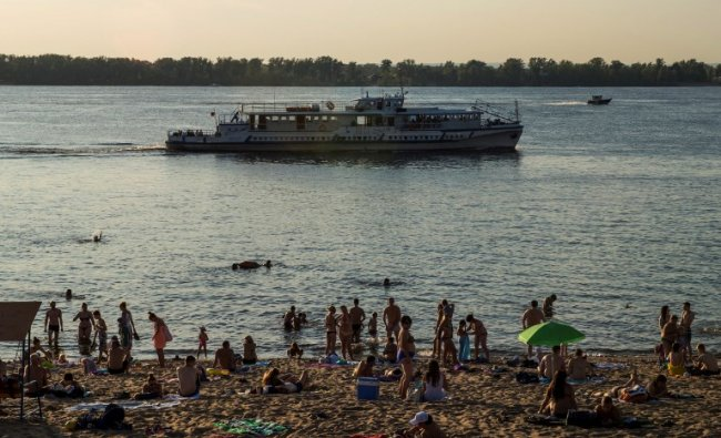 A tourist boat passes as people sunbathe at a beach on the Volga River in downtown Samara on August 23, 2017. AFP Photo