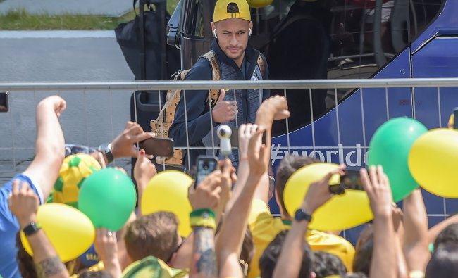 Fans cheer as Brazil\'s forward Neymar gives a thumbs up upon his arrival with teammates at Mirage Hotel in Kazan for their Russia 2018 World Cup round of 8 football match against Belgium. Credit: LUIS ACOSTA / AFP