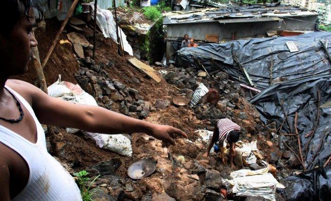 Residents look for belongings after a landslide on cluster of two slums...
