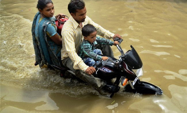 Commuters wade through a waterlogged street after heavy rains ...