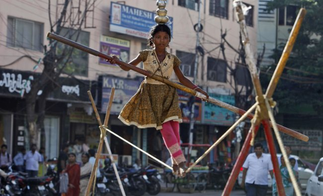 A child street artist walks a tightrope in Hyderabad