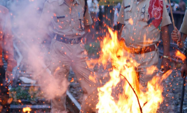 Railway policemen stand near a burning effigy representing the Indian government during a SP protest