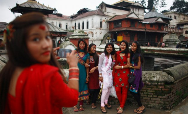 Nepalese women pose for a picture during the Rishi Panchami festival, in Kathmandu ...