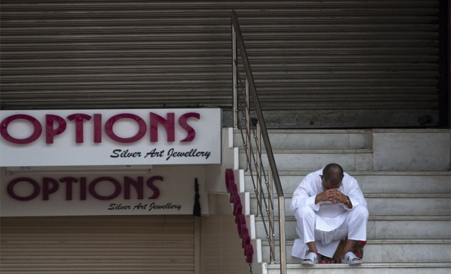 A resident in front of closed shops at Lajpat Nagar market in New Delhi ...