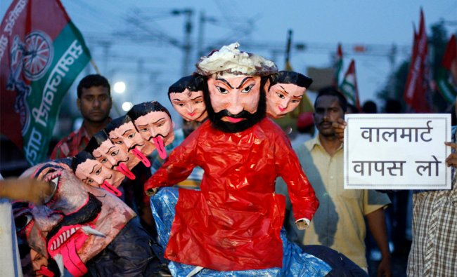 Samajwadi Party activists hold an effigy of Manmohan singh during a protest...