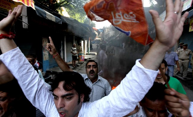 BJP shout anti government slogans in front of burning tyres during a one day strike in Jammu...