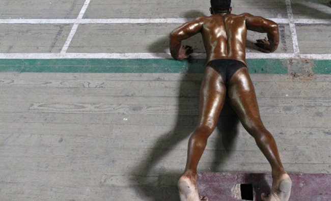A participant does push-ups backstage during a bodybuilding competition in Srinagar...