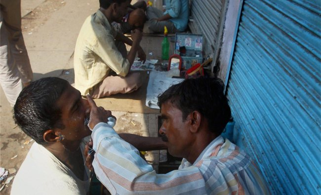 Barbers doing their business outside closed shops
