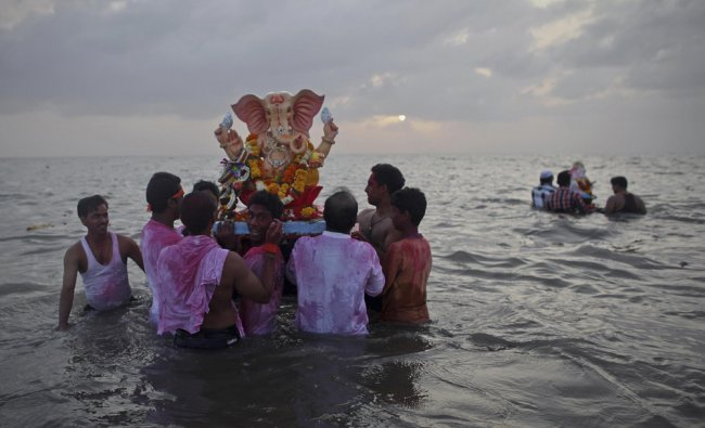 Devotees carry a statue of the Hindu god Ganesh