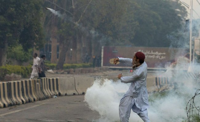 A supporter throws a teargas canister during clashes along a road