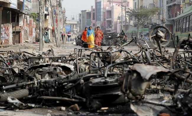 Women walk past charred vehicles in a riot affected area following clashes between people demonstrating for and against a new citizenship law in New Delhi, India. (Reuters Photo)