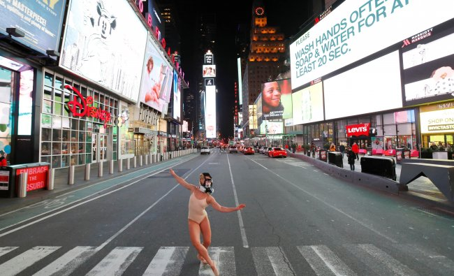 Ballet dancer and performer Ashlee Montague of New York wears a gas mask while she dances in Times Square. (Credit: Reuters)
