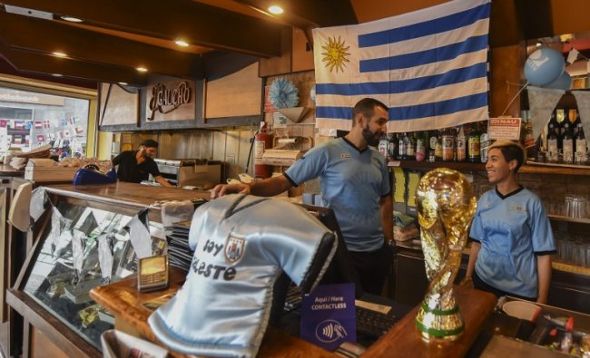 A flag of Uruguay, a replica of the World Cup trophy and a jersey are displayed at a bar in Montevideo in support of the national football team taking part in the FIFA World Cup. The quarter-final match between Uruguay and France is on July 6, 2018. Credit: Miguel ROJO / AFP