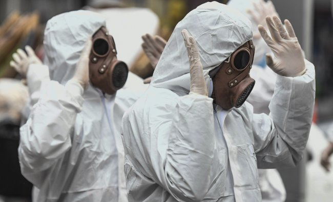 Youngsters wearing protective suites take part in a performance as part of an awareness campaign against the spread of the new coronavirus, COVID-19, in Bogota. (Credit: AFP)