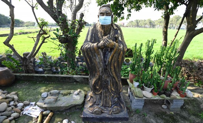 This picture shows a masked Chinese prophet Confucius statue, part of a collection by Taiwan's sculptor Lin Hsin-lai, in Taoyuan, northern Taiwan. (Credit: AFP)