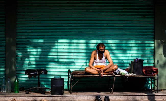 A security guard rests sitting on a cot in front of a closed shop during a government-imposed nationwide lockdown as a preventive measure against the spread of the COVID-19. (AFP Photo)