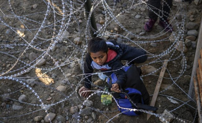 Kevin Andres, a Mexican migrant child from Oaxaca, crawls to get his backpack from the barbed wire after jumping the border fence to get into the U.S. side to San Diego, Calif., from Tijuana, Mexico. AP/PTI