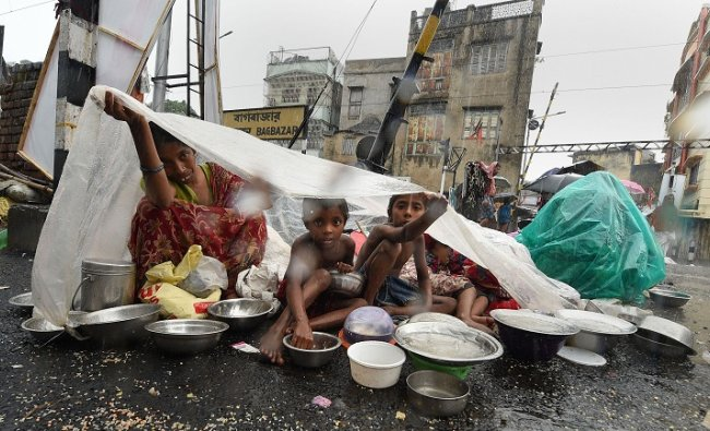 A family sits under a polythene sheet during rain in Kolkata. PTI