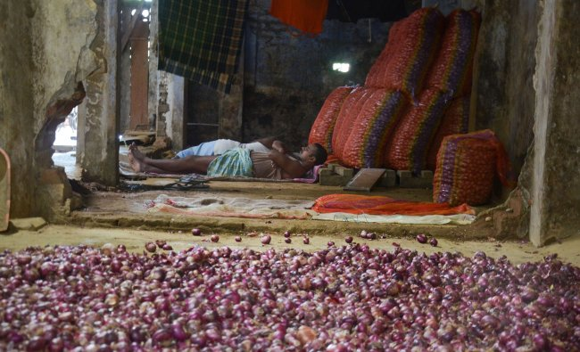 A labourer rests beside onion sacks at a market in Dibrugarh. PTI