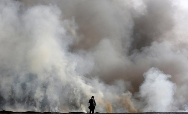 A man stands as he looks at the smoke coming out from a chemical and a cloth warehouse after a fire broke out on the banks of river Ganges in Kolkata, India June 8, 2019. REUTERS/Rupak De Chowdhuri