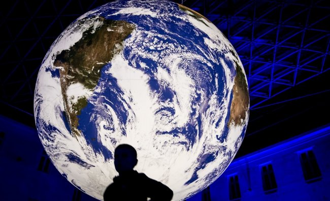 A visitor stands in front of the installation Gaia created by British artist Luke Jerram, that is presented in Bratislava. (AFP)