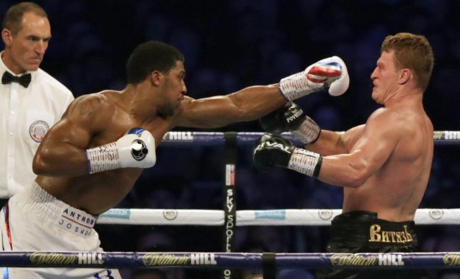 Russia\'s Alexander Povetkin (2nd L) falls backwards as Britain\'s Anthony Joshua (R) throws a punch to knock him to the canvas in the 7th round during their boxing world Heavyweight title fight at Wembley Stadium in north west London on September 22, 2018. - Britain\'s Anthony Joshua retained his International Boxing Federation, World Boxing Association and World Boxing Organisation heavyweight titles with a seventh-round stoppage of Alexander Povetkin at London\'s Wembley Stadium on September 22, 2018. AP PTI