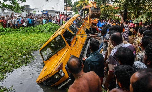 A play school van being pulled out of a temple pond after an accident at Maradu in Ernakulam district on Monday. PTI Photo