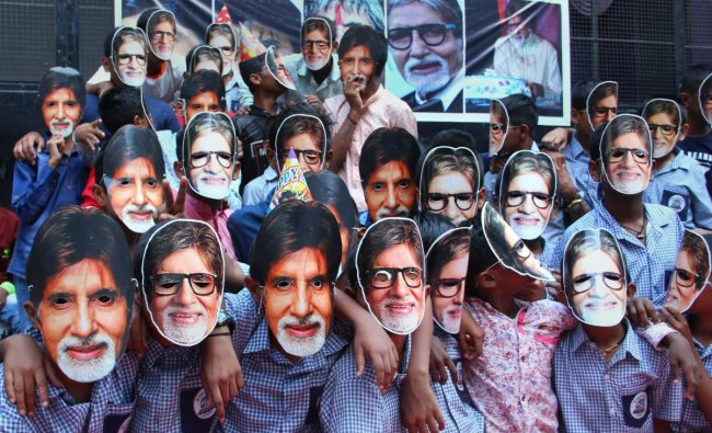 Fans wear masks of Bollywood actor Amitabh Bachchan as they celebrate his 76th birthday, in Pune on Thursday. (PTI photo)