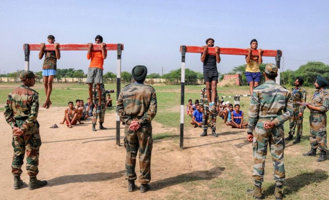Army officer watch candidates perform pull-ups during an army recruitment rally at Khasa, approximately 15 Kms from Amritsar on Saturday. (AP/PTI Photo)